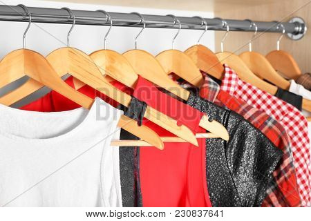 Hangers with different clothes in wardrobe closet