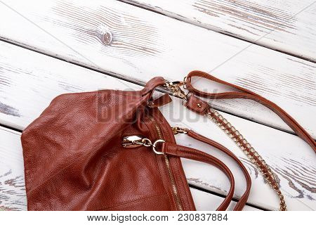 Close Up Brown Leather Satchel. Handle On Purse. White Wooden Desks Surface Background.