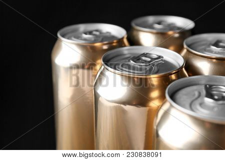 Cans of beer on black background, closeup