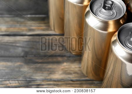 Cans of beer on wooden background, closeup
