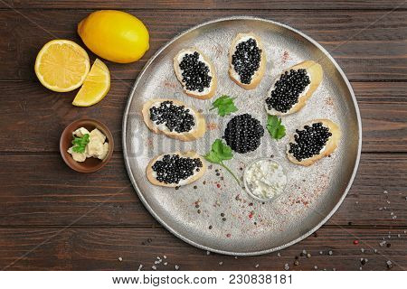 Sandwiches with delicious black caviar on metal tray