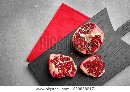 Wooden board with ripe pomegranate on grey background