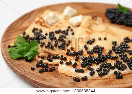 Thin pancakes with delicious black caviar on wooden plate