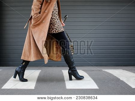 Stylish woman in black shoes walking across the street