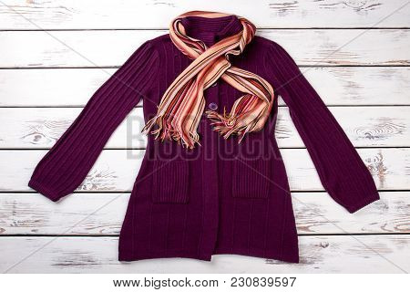 Purple Sweater Coat With Scarf. Flat Lay Front View Burgundy Color Pullover. Bright Wooden Desk Back