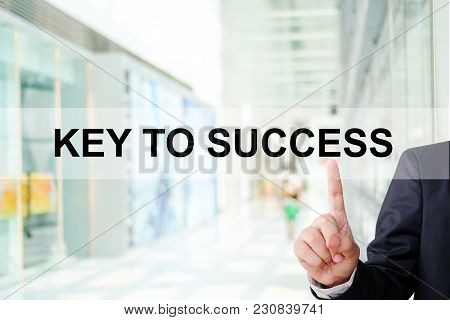 Businessman Finger Touch Key To Success Word On Blur Office Background, Business Concept