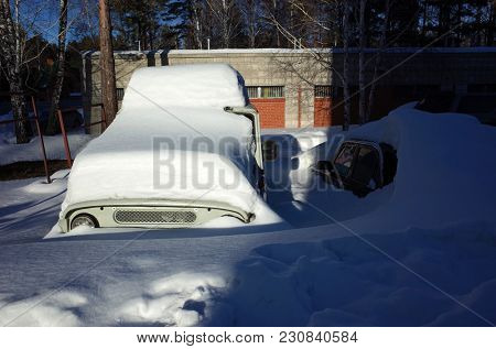 Russia, Koltsovo - March 11, 2018: Old russian cars buried under thick layer of snow on parking in Siberia