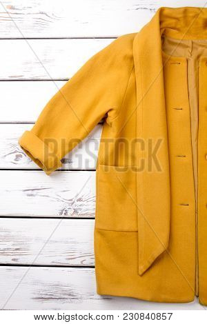 Rolled Up Yellow Coat Sleeve. Cropped Vertical View. White Desk Wooden Background.