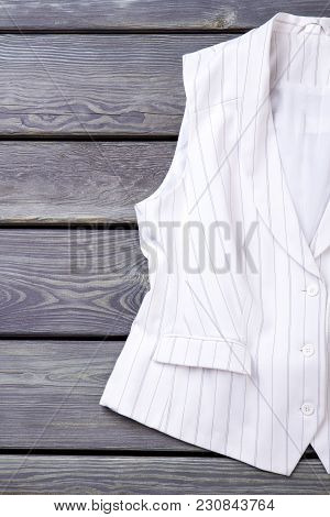 Close Up White Sleeveless Business Jacket. Vertical View, Wooden Desk Surface Background.