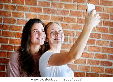 Smiling female friends taking a selfie