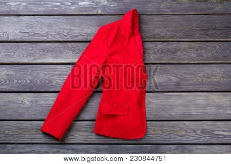 Folded Red Woman Coat. Grey Wooden Surface Background. Flat Lay, Top View.