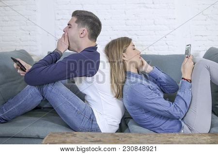 Young Attractive And Tired Internet Addict Couple Using App On Mobile Phone Ignoring Each Other Sitt