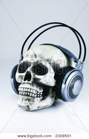 Human skull with large gray headphones x poster
