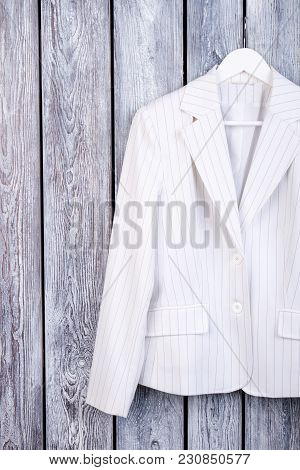 White Suit Jacket On Hanger. Dark Wooden Background. Top View.