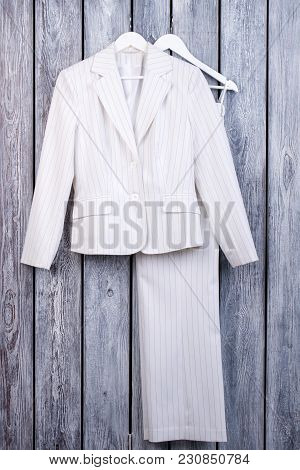 White Business Suit On Hanger. Striped Jacket And Trousers, Top View.