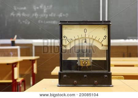 Educational galvanometer with not real number 555 on yellow desk in empty physics school class; formula on blackboard