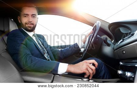 View from the side confident businessman sits at the wheel of a car