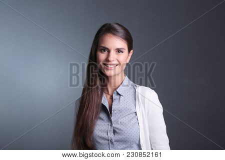Portrait of a businesswoman , against dark background. Woman smiling. Portrait of a woman