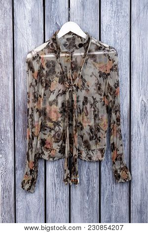 Abstract Woman Blouse On Hanger. Grey Desk Surface Background.