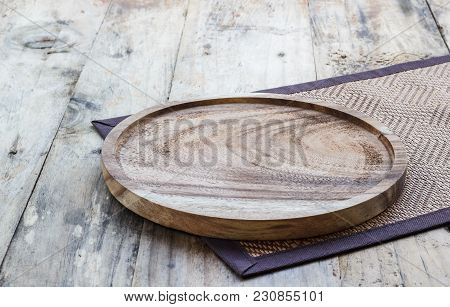 Empty Wooden Plate On Wood Table. Copy Space. Wood Plate For Food Or Vegetable Serving To Customers.