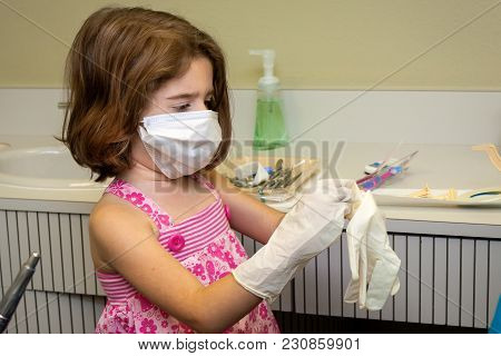 A Little Girl At The Denist Office Tries On A Surgical Mask And Latex Gloves   She Looks Serious As
