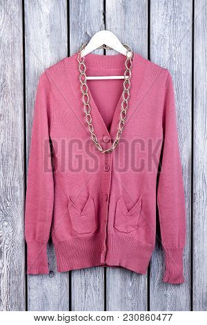 Pink Wool Coat With Accessorie, Flat Lay. Top View, Knitted Cardigan On Hanger. Dark Wooden Desk Sur
