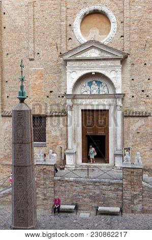 URBINO, ITALY - JUNE 14, 2017: People at the Gothic church of San Domenico and Egyptian obelisk. This is one of the twelve original Egyptian obelisks in Italy moved from Rome in 1737