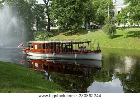 RIGA, LATVIA - JUNE 18, 2017: People on the tour boat in city canal. Boat tour by canal and Daugava river is one of Must Do for tourists in Riga
