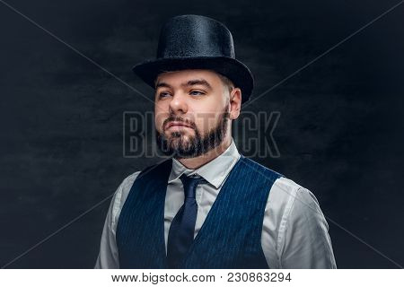 Close Up Portrait Of Elegant Bearded Male Wearing Waistcoat, Bow Tie And Cylinder Hat On Grey Backgr