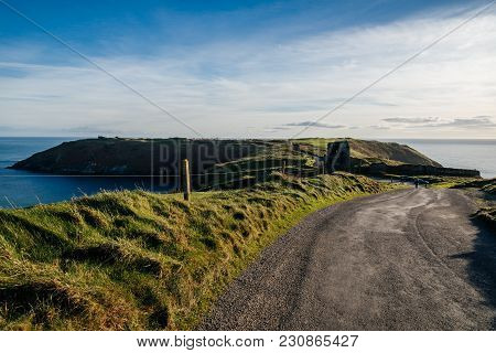 Scenic View Of The Road To Old Head Of Kinsale With Green Hills At Sunset.