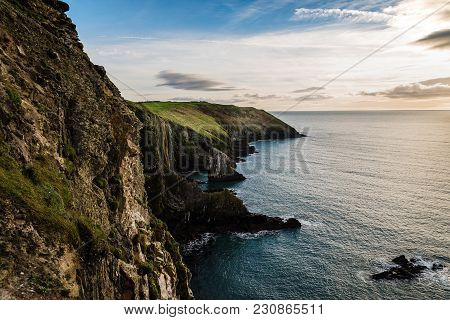 Scenic View Of Cliffs In  Old Head Of Kinsale Peninsula In Ireland With Green Hills At Sunset.