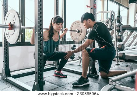 Woman Flexing Muscles With Barbell