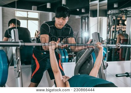 Asian Male Personal Trainer Helping A Young Woman Lift A Barbell While Working Out In A Gym.