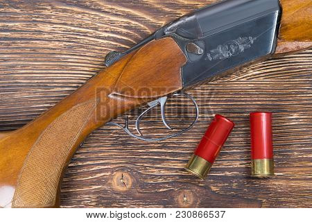Two Red Cartridges On A Dark Wooden Board, And A Hunting Rifle