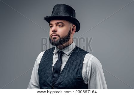 Portrait Of Elegant Bearded Male Dressed In A Waistcoat And A Cylinder Hat Isolated On Grey Backgrou