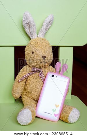 Light Brown Bunny Toy Sitting On Green Chair And Holding White Phone With Pink Bunny Ears As Birthda