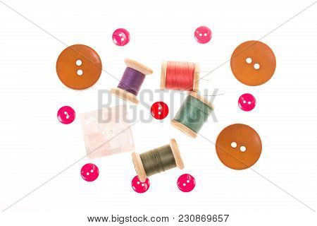 Few Wooden Spools Of Thread And Colour Buttons On White