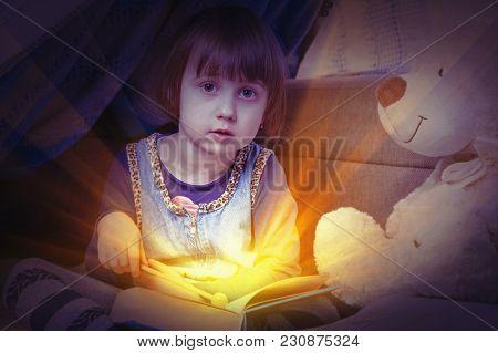 Cute Child Girl Reading A Magic Book. (education, Knowledge, Wisdom, Magic, Childhood Concept)