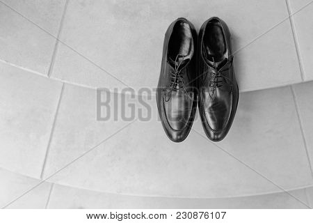 Man Shoes On Floor Close Up Black Color. Expensive Shining Polished Leather Male Shoes Standing At N