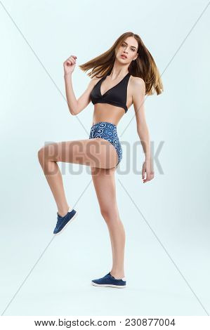 Young Beautiful Woman Doing Fitness Exercises. Full Length Portrait. Caucasian Girl Actively Engaged