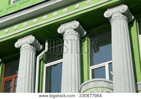 Restored Old Multi-storey Building With Antique Columns, Painted In Green