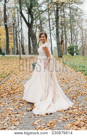 Beautiful Bride With A Wedding Bouquet In Their Hands Outdoors In A Park