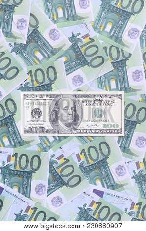 100 Dollars Bill Is Lies On A Set Of Green Monetary Denominations Of 100 Euros. A Lot Of Money Forms
