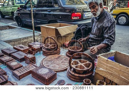 Tehran, Iran - October 15, 2016: Old Man Sells Product Made Of Wood On A Pavement In Tehran