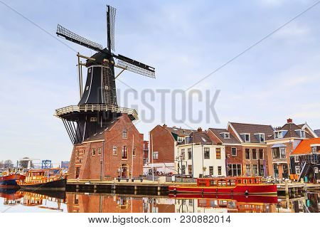 Windmill And Traditional Houses In Haarlem, Holland, Netherlands