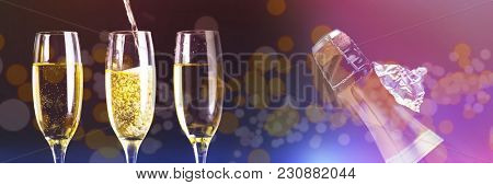 Two full glasses of champagne and one being filled against top of bottle of champagne with ripped foil