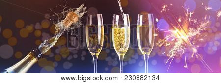 Two full glasses of champagne and one being filled against champagne cork popping