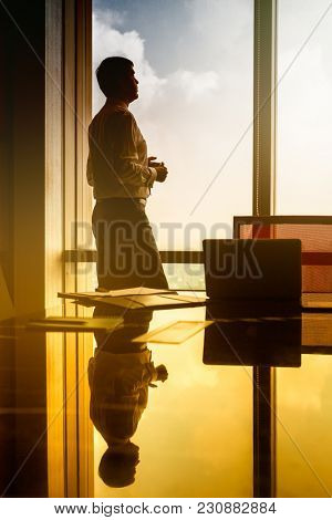 Indian business man standing on office window in pensive posture looking at city, filtered image