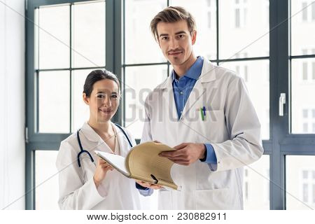 Portrait of two dedicated doctors smiling and looking at camera while holding a tablet and a folder with medical records