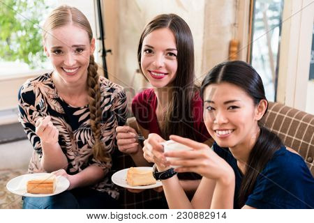 Three young women sharing opinions and ideas while eating cake indoors